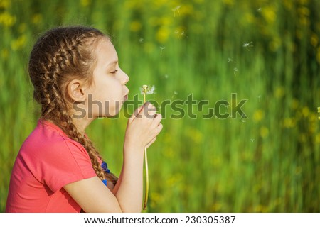 Beautiful little girl blowing on white dandelion in green summer park. - stock photo