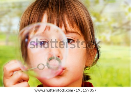 Beautiful little  girl blowing soap bubbles indoor - stock photo