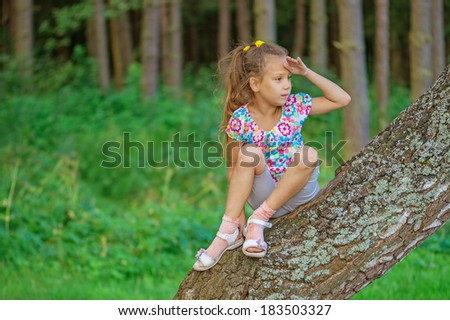 Beautiful little girl climbed on tree forest and stares into distance. - stock photo
