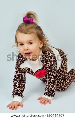 Beautiful little girl crawling on the floor - stock photo