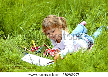 beautiful little girl draws on nature - stock photo