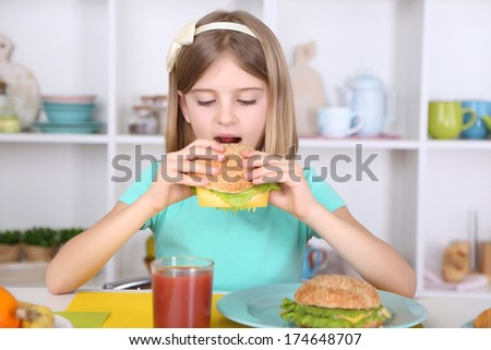 Beautiful little girl eating breakfast in kitchen at home - stock photo