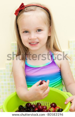Beautiful little girl eating strawberries and cherries - stock photo
