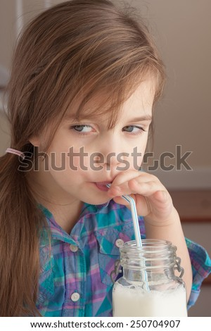 Beautiful little girl enjoying a glass of milk with a straw - stock photo