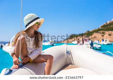 Beautiful little girl enjoying sailing on boat in the open sea - stock photo