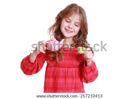 Beautiful little girl having a cup of tea playing with miniature tea set - stock photo