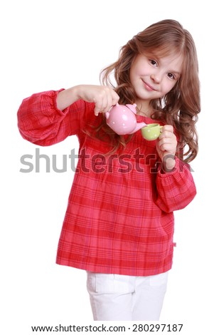 Beautiful little girl having a cup of tea playing with miniature tea set/Serene chool girl making tea - stock photo