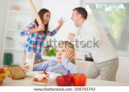 Beautiful little girl having breakfast in the kitchen and listening quarrel of parents. She is sadness and upset, holding head and looking away. - stock photo
