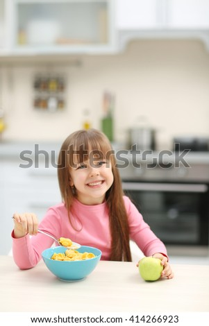 Beautiful little girl having breakfast with cereal and apple in kitchen - stock photo