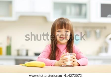 Beautiful little girl having breakfast with milk and banana in kitchen - stock photo