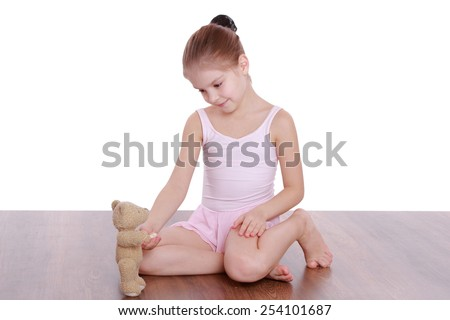 Beautiful little girl holding a teddy bear and is engaged in gymnastics on a wooden floor on a white background - stock photo