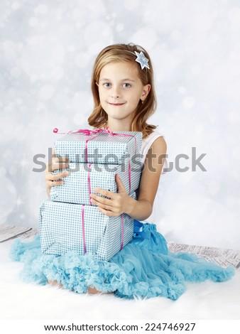 Beautiful little girl holding christmas presents - stock photo