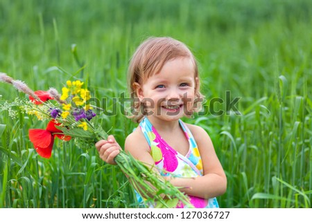 Beautiful little girl in a meadow with a bouquet of flowers - stock photo