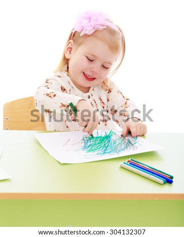 Beautiful little girl in a Montessori kindergarten is sitting at her Desk. The girl draws with a marker on a white sheet of paper and smiles. Closeup-Isolated on white background - stock photo