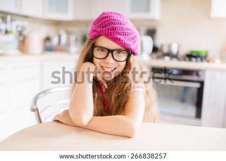 Beautiful little girl in a red cap sits at a table in the kitchen and smiling. - stock photo