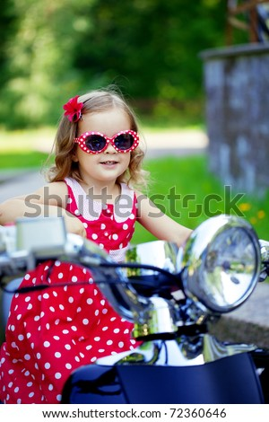 Beautiful little girl in a red dress on a motorcycle - stock photo