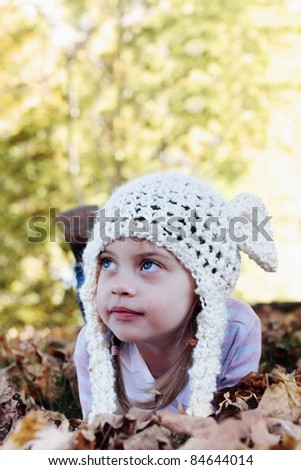 Beautiful little girl in a white bobble hat lying in the leaves and looking away from the camera. Selective focus on little girls face with shallow DOF. - stock photo