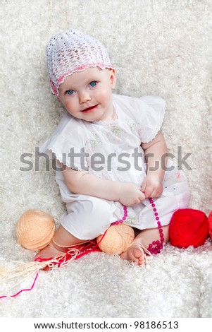 beautiful little girl in a white dress with balls of threads - stock photo