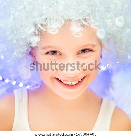 beautiful little girl in a white wig near the Christmas tree - stock photo