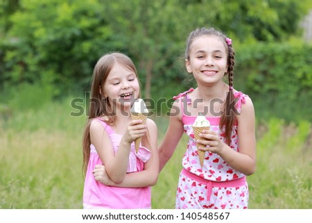 Beautiful little girl in casual clothes eat ice cream on a background of nature in spring - stock photo