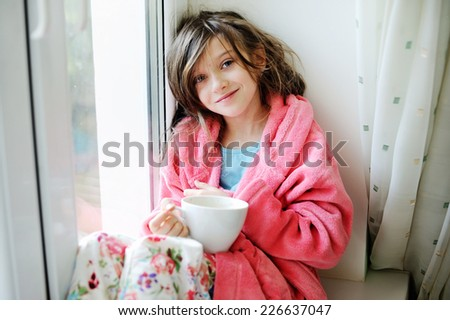 Beautiful little girl in cozy pink bathrobe drinking tea from white  cup on the window - stock photo