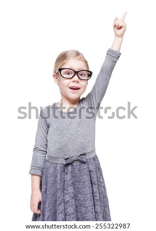Beautiful little girl in glasses showing on something by finger isolated  - stock photo