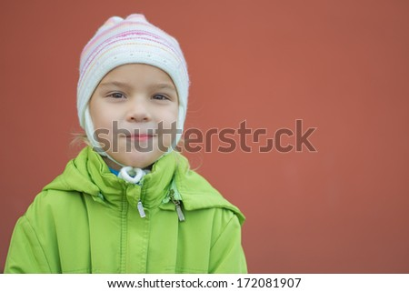 Beautiful little girl in green jacket and hat of profile on red background. - stock photo