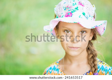 Beautiful little girl in hat on background of green summer city park. - stock photo
