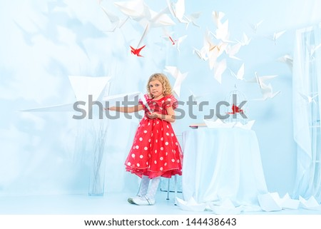 Beautiful little girl in her  dream world feeding paper birds. - stock photo