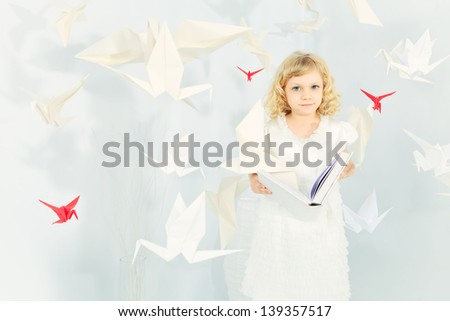 Beautiful little girl in her dream world surrounded with paper birds, reading fairytales. - stock photo
