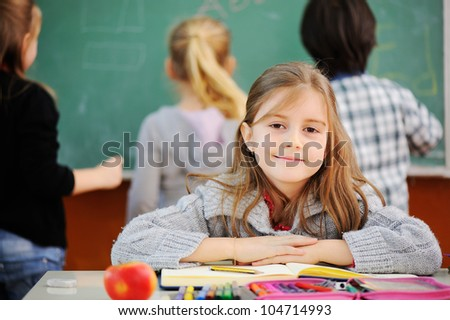 Beautiful little girl in school with her friends - stock photo