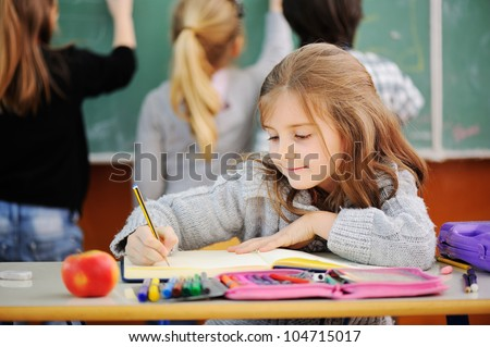 Beautiful little girl in school with her friends in background - stock photo