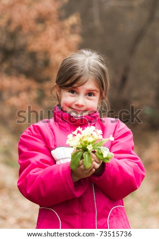 Beautiful little girl in spring holding primrose in hands - stock photo