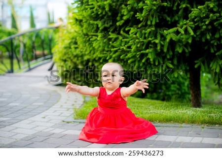 beautiful little girl in spring park park in red pulling her hands to her mother - stock photo