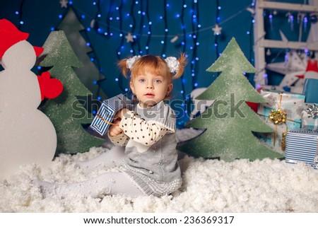 beautiful little girl in the snow. fabulous decor - stock photo