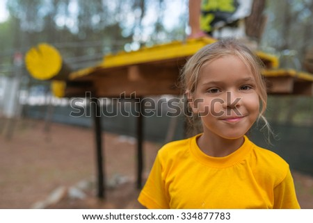 Beautiful little girl in yellow blouse on the playground. - stock photo