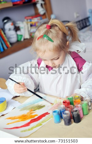 Beautiful little girl is drawing with gouaches on paper - stock photo