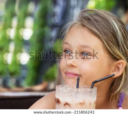 beautiful little girl is drinking a milkshake  - stock photo