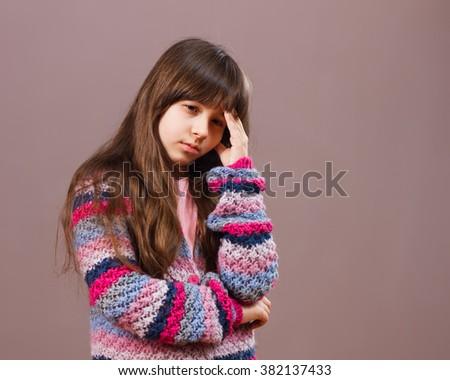 Beautiful little girl is having a headache.Sad little girl with headache  - stock photo