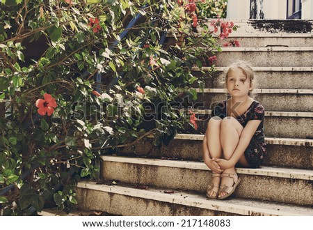Beautiful little girl is sitting on old stairs near flowers, Greece - stock photo