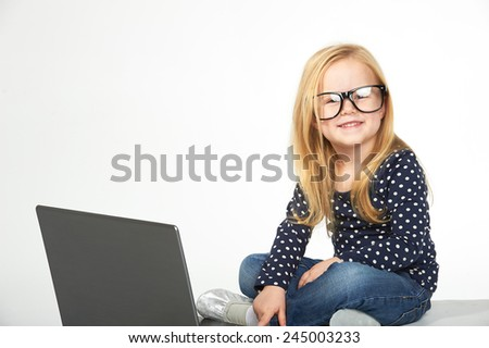 Beautiful little girl learning at the computer - stock photo
