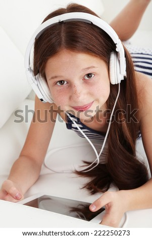 Beautiful little girl listening to music on sofa in room - stock photo