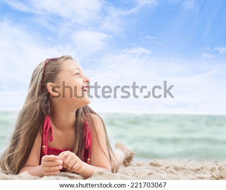 beautiful little girl lying on the sandy sea beach - stock photo
