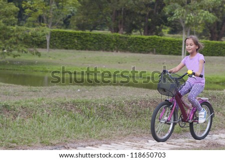 Beautiful Little Girl On Bicycle Ride At Park - stock photo
