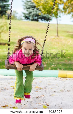 Beautiful little girl on the swing - stock photo