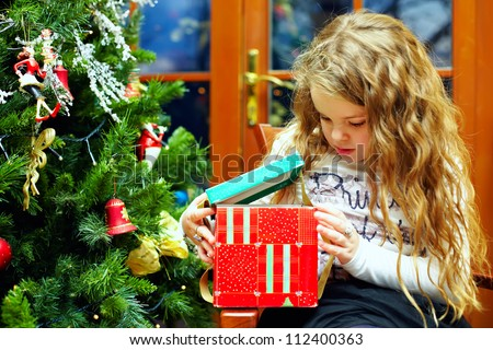 beautiful little girl opens a gift box, christmas interior - stock photo