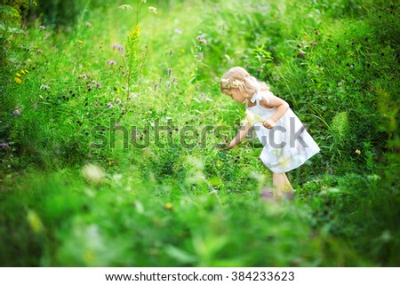 Beautiful little girl picking flowers in a meadow. Summer sunny day, lots of greenery and flowers. In the baby on her head a crown of flowers, and in his hand a bouquet. Blonde girl in white dress. - stock photo