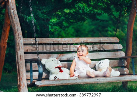 Beautiful little girl playing on a wooden bench in a green park - stock photo