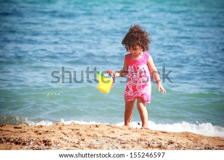 Beautiful little girl playing on the beach - stock photo