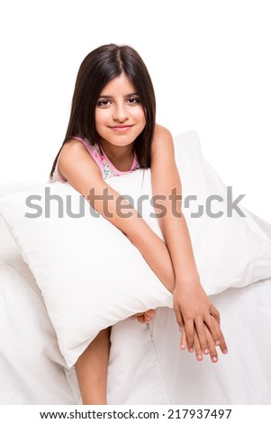 Beautiful little girl relaxing on her bed - stock photo